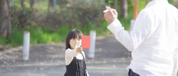 レッドカードを出す子供の画像